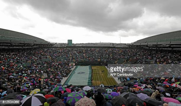 TOPSHOT Ground staff prepare the court covers as rain stops play ahead of the women's singles quarterfinal match between Spain's Garbine Muguruza and...