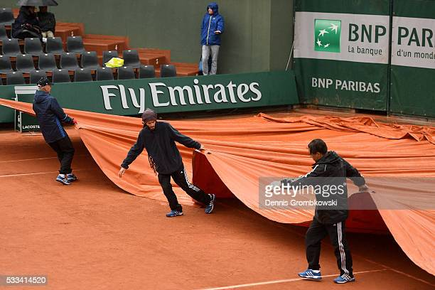 Ground staff pull on the covers as rain causes play to be abandoned for the day on day one of the 2016 French Open at Roland Garros on May 22 2016 in...