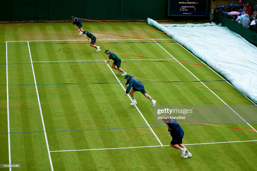 Ground staff pull the covers onto court 18 as rain delays play during day four of the Wimbledon Lawn Tennis Championships at the All England Lawn Tennis and Croquet Club on July 1, 2016 in London, England.