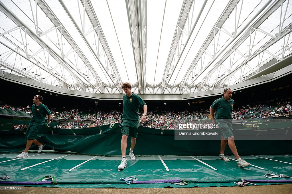Ground staff pull the rain covers off Centre Court under a closed roof after rain interrupted play during the Ladies' Singles second round match between Agnieszka Radwanska of Poland and Mathilde Johansson of France on day four of the Wimbledon Lawn Tennis Championships at the All England Lawn Tennis and Croquet Club on June 27, 2013 in London, England.