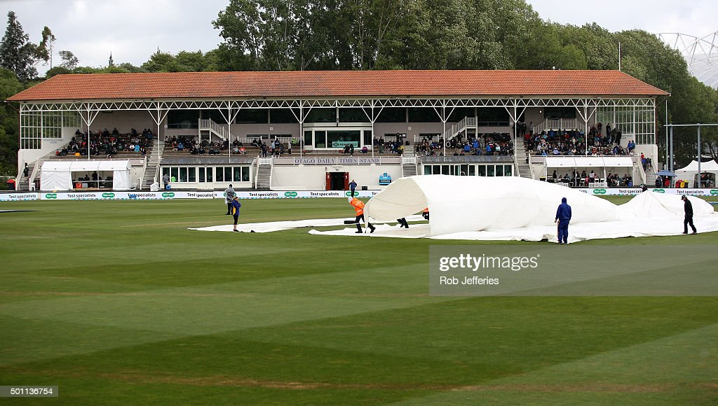 Ground staff put covers on due to rain during day four of the First Test match between New Zealand and Sri Lanka at University Oval on December 13...