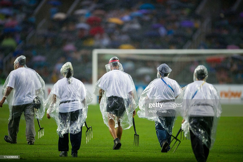 Ground staff remove excess water from the pitch using forks as heavy rain falls prior to the Barclays Asia Trophy Semi Final match between Tottenham Hotspur and Sunderland at Hong Kong Stadium on July 24, 2013 in So Kon Po, Hong Kong.