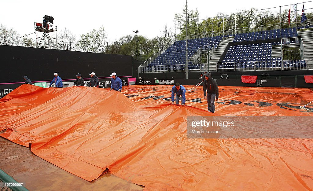 Ground staff remove the rain covers after rain stopped play during day one of the Fed Cup World Group Play-Offs between Switzerland and Australia at Tennis Club Chiasso on April 20, 2013 in Chiasso, Switzerland.