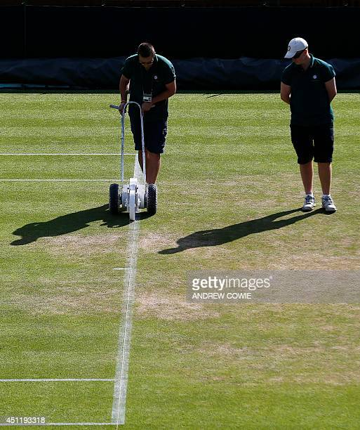 Ground staff repaint the baseline of a court before the start of day three of the 2014 Wimbledon Championships at The All England Tennis Club in...