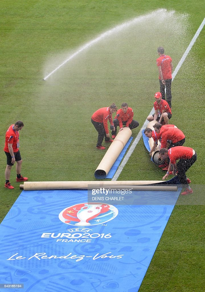 Ground staff roll a carpet before the Euro 2016 round of 16 football match between Germany and Slovakia at the Pierre-Mauroy stadium in Villeneuve-d'Ascq, near Lille, on June 26, 2016. / AFP / DENIS