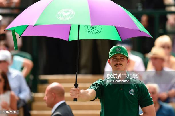 A ground staff shields Switzerland's Timea Bacsinszky from the sun with an umbrella during her women's singles third round match against Poland's...
