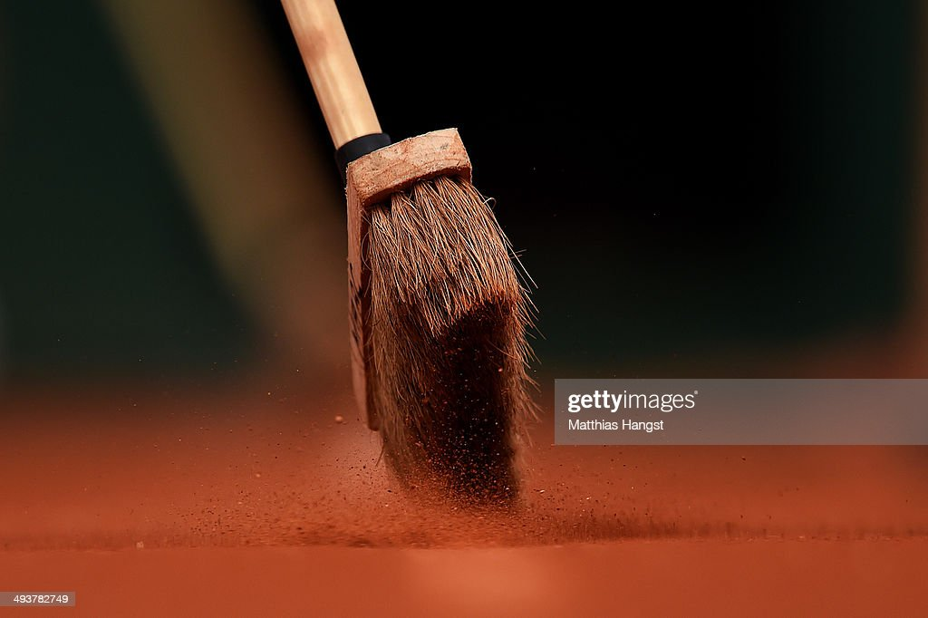 Ground staff sweep the loose clay from the lines on court during day one of the French Open at Roland Garros on May 25, 2014 in Paris, France.