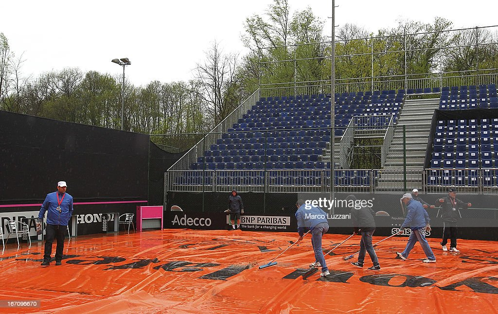 Ground staff use squeegees to remove rain water from the covers after rain stopped play on day one of the Fed Cup World Group Play-Offs between Switzerland and Australia at Tennis Club Chiasso on April 20, 2013 in Chiasso, Switzerland.