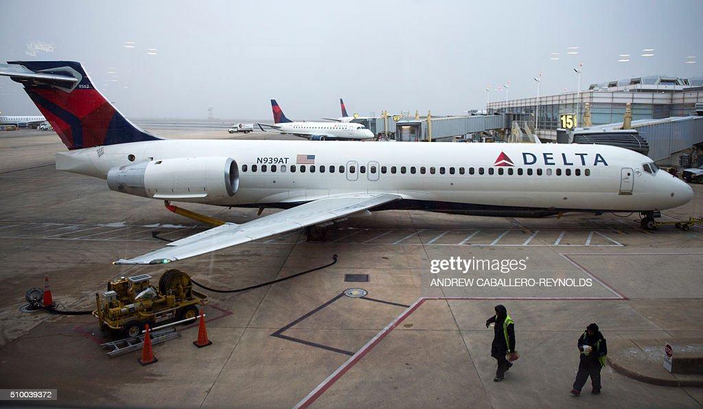Ground staff walk past a Delta plane parked in the terminal at Ronald Regan National Airport in Washington, DC, on February 13, 2016. / AFP / ANDREW CABALLERO-REYNOLDS