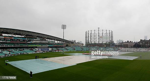 Ground staff work on the pitch as rain delays the start of the fourth day's play of the fifth Ashes cricket Test match between England and Australia...