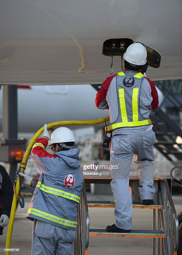 Ground staff work under a Japan Airlines Co. (JAL) aircraft at Haneda Airport in Tokyo, Japan, on Tuesday, Nov. 5, 2013. JAL, Japan's second-largest carrier, raised its full-year profit outlook on Oct. 31 as it expects demand to increase on its Southeast Asia routes. Photographer: Akio Kon/Bloomberg via Getty Images
