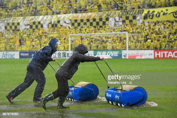 Ground staffs attempt to sweep water off the pitch as the game is delayed due to heavy rain prior to the JLeague J1 match between Kashiwa Reysol and...