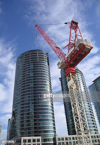 A ground view of a crane working on skyscrapers