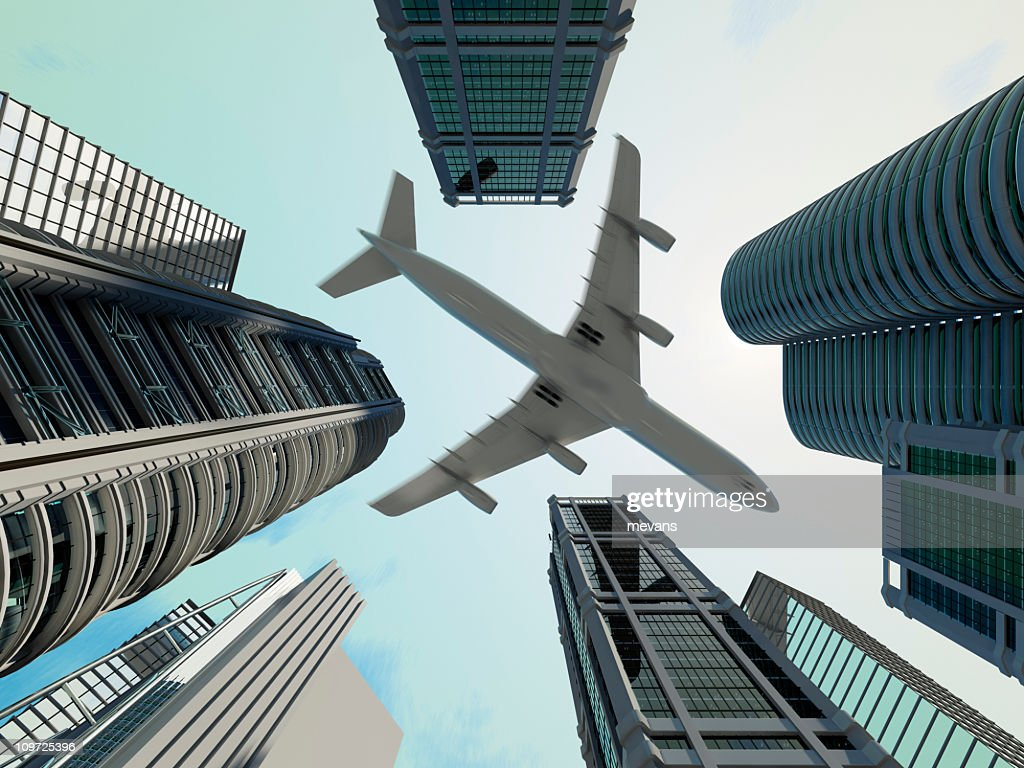 Ground view of jet flying over skyscrapers in the city : Stock Photo