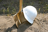 A hard hat and golden shovel await  their use in a groundbreaking ceremony.