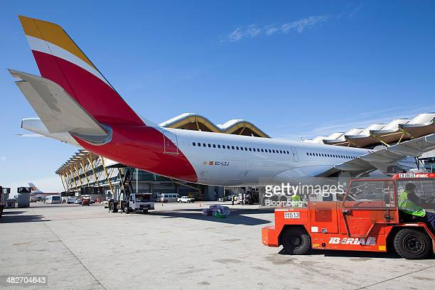 Groundcrew work near an Airbus A330300 jet operated by Iberia airlines a unit of International Consolidated Airlines Group SA as it stands at a...