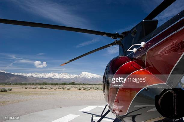 Grounded red Hughes helicopter in the desert on a clear day