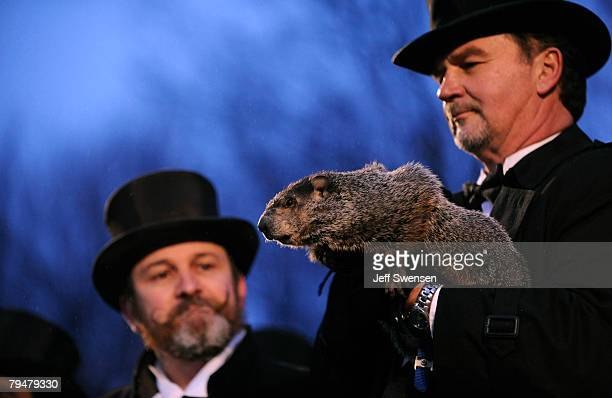 Groundhog handler Ben Hughes looks at Punxsutawney Phil while cohandler John Griffiths holds him after he saw his shadow predicting 6 more weeks of...
