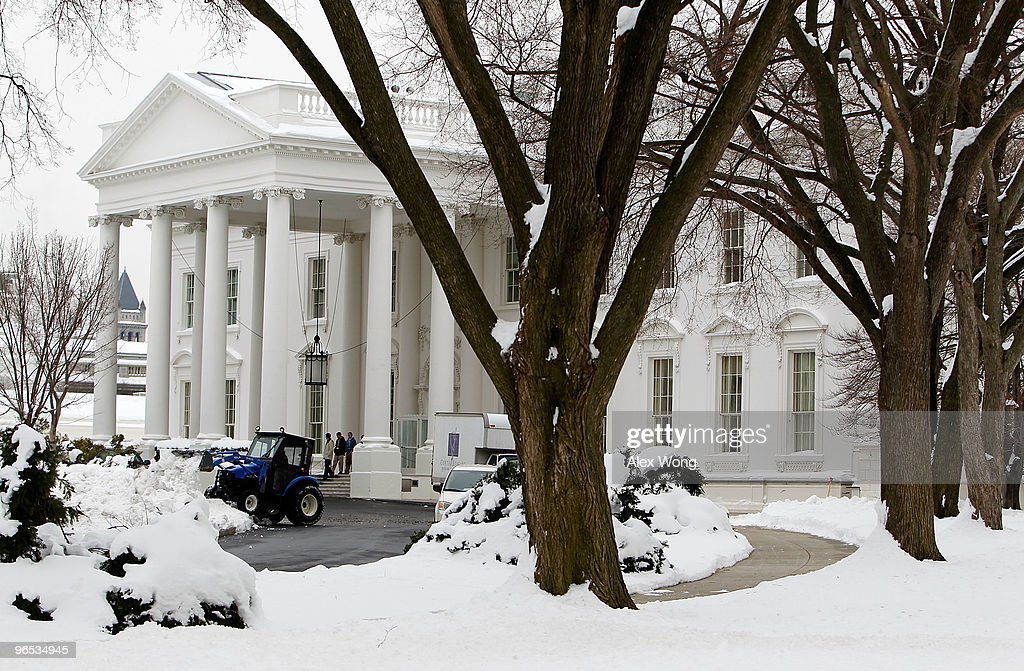 A groundkeeper plows snow from the last snowstorm on a driveway of the White House as visitors come out from the North Portico February 9 2010 in...