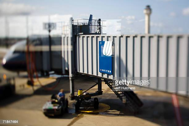 JUNE 28 2006 Grounds crew do last minute work as the gangway is extended to an outbound United Airlines flight at Chicagos OHare airport as airline...