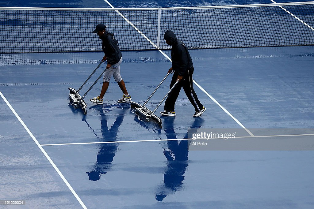 Grounds crew dry the court after rain suspened action during Day Nine of the 2012 US Open at USTA Billie Jean King National Tennis Center on September 4, 2012 in the Flushing neighborhood of the Queens borough of New York City.