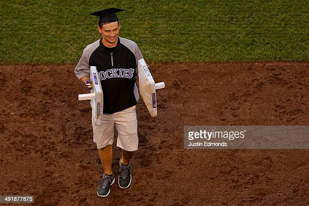 Grounds crew member Nik Wooldridge changes out bases during the third inning of a game between the San Diego Padres and Colorado Rockies wearing a...