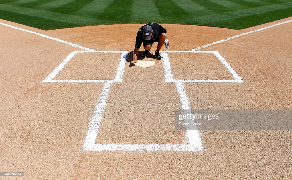 A grounds crew member paints home plate before a game between the Miami Marlins and the Detroit Tigers at Roger Dean Stadium on March 6, 2012 in Jupiter, Florida.
