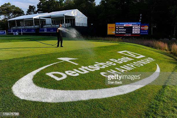 A grounds crew member sprays water on a Deutsche Bank Championship logo on the 16th hole during the second round of the Deutsche Bank Championship at...