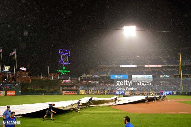 Grounds crew members roll out tarps to protect the field from saturation in the third inning during a 90 minute rain delay between the Philadelphia...