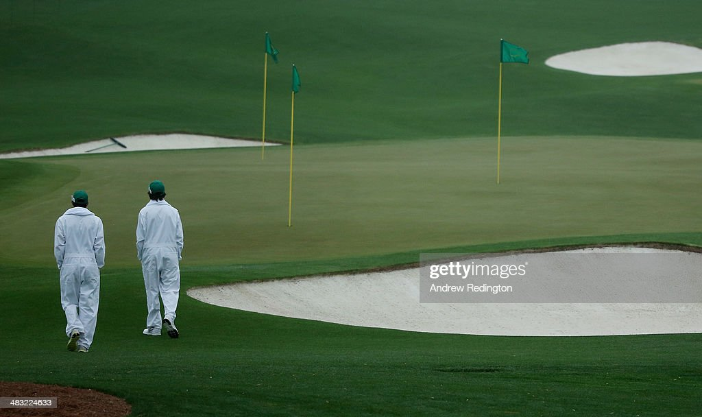 Grounds crew members tend to the greens during a practice round prior to the start of the 2014 Masters Tournament at Augusta National Golf Club on April 7, 2014 in Augusta, Georgia.