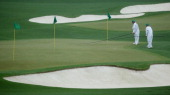 Grounds crew members tend to the greens during a practice round prior to the start of the 2014 Masters Tournament at Augusta National Golf Club on...