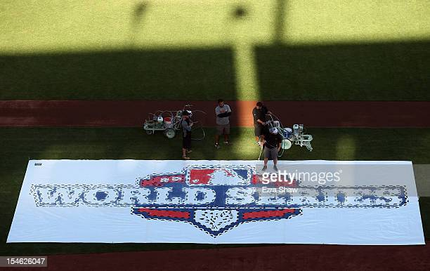 Grounds crew paint the World Series logo on the grass outside the first base line before World Series Media Day at ATT Park on October 23 2012 in San...