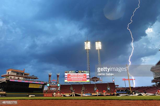 Grounds crew pull the tarp on the field as lightning from an approaching storm strikes in the distance during the third inning of a game between the...