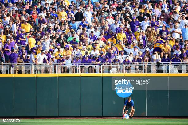 Grounds crew remove beach balls from the field as Louisiana State University takes on the University of Florida during the Division I Men's Baseball...
