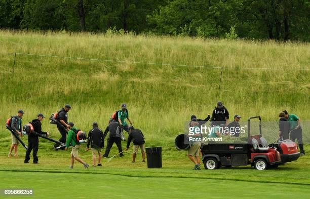 Grounds crew work on the fourth hole during a practice round prior to the 2017 US Open at Erin Hills on June 13 2017 in Hartford Wisconsin