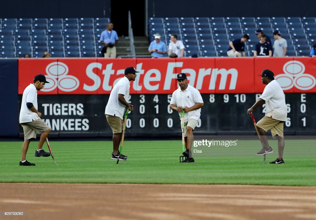Grounds crew workers try and improve the drainage in the outfield during the game between the New York Yankees and the Detroit Tigers on August 2, 2017 at Yankee Stadium in the Bronx borough of New York City.
