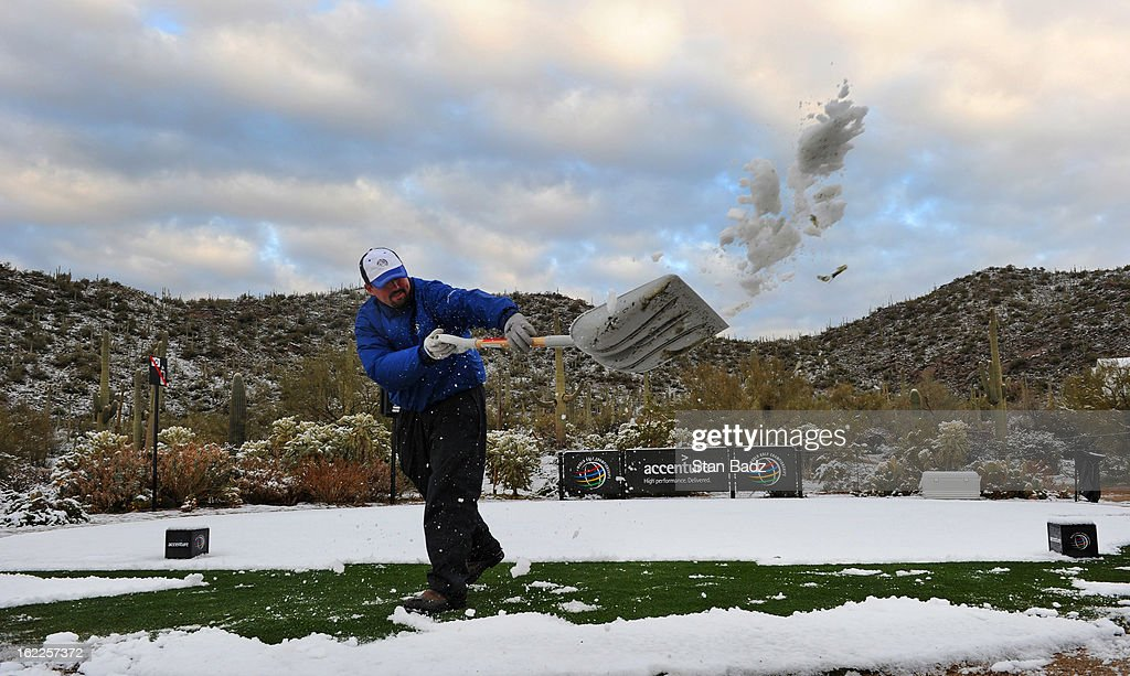 Grounds crewman Mike Pierce shovels snow from the 17th tee box before the restart of the first round of the World Golf Championships-Accenture Match Play Championship at The Golf Club at Dove Mountain on February 21, 2013 in Marana, Arizona.