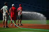 Grounds crewmen water the infield prior to the MLB game between the Chicago White Sox and the Los Angeles Angels of Anaheim at Angel Stadium of...