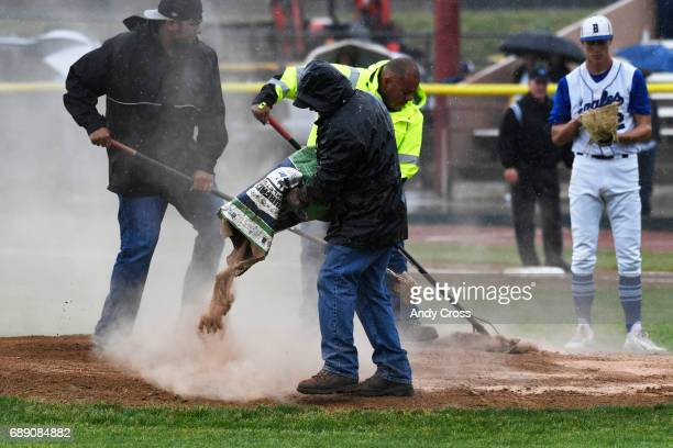 Grounds crews apply diamond dry to the pitching mound while Broomfield Eagles pitcher Blake Rohm #2 waits during a steady heavy rain in the first...