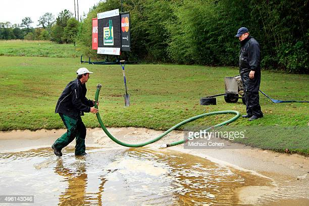 Grounds crews drain the bunkers after heavy rains during a continuation of the second round of the Sanderson Farms Championship at The Country Club...