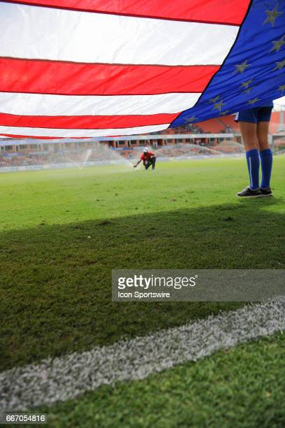 Grounds keepers adjust sprinklers as flag bearers hold the American Flag before the USA Soccer match between USA and Russia on April 9 2017 at BBVA...