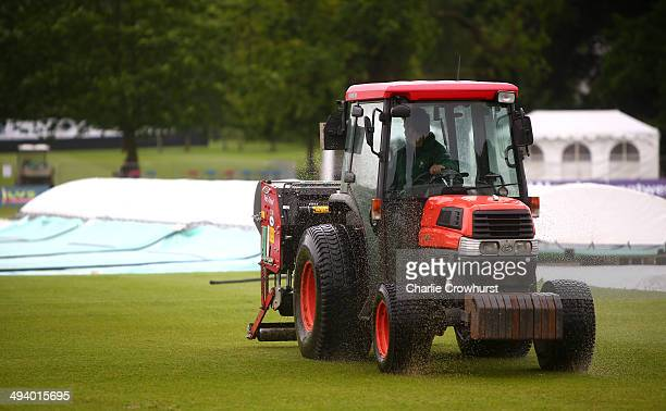A grounds man tries to clear surface water from the outfield as the rain covers come on and the start of play is delayed during day two of the LV...