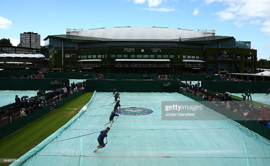 Grounds staff pull the covers off on the outside courts on day five of the Wimbledon Lawn Tennis Championships at the All England Lawn Tennis and Croquet Club on July 1, 2016 in London, England.