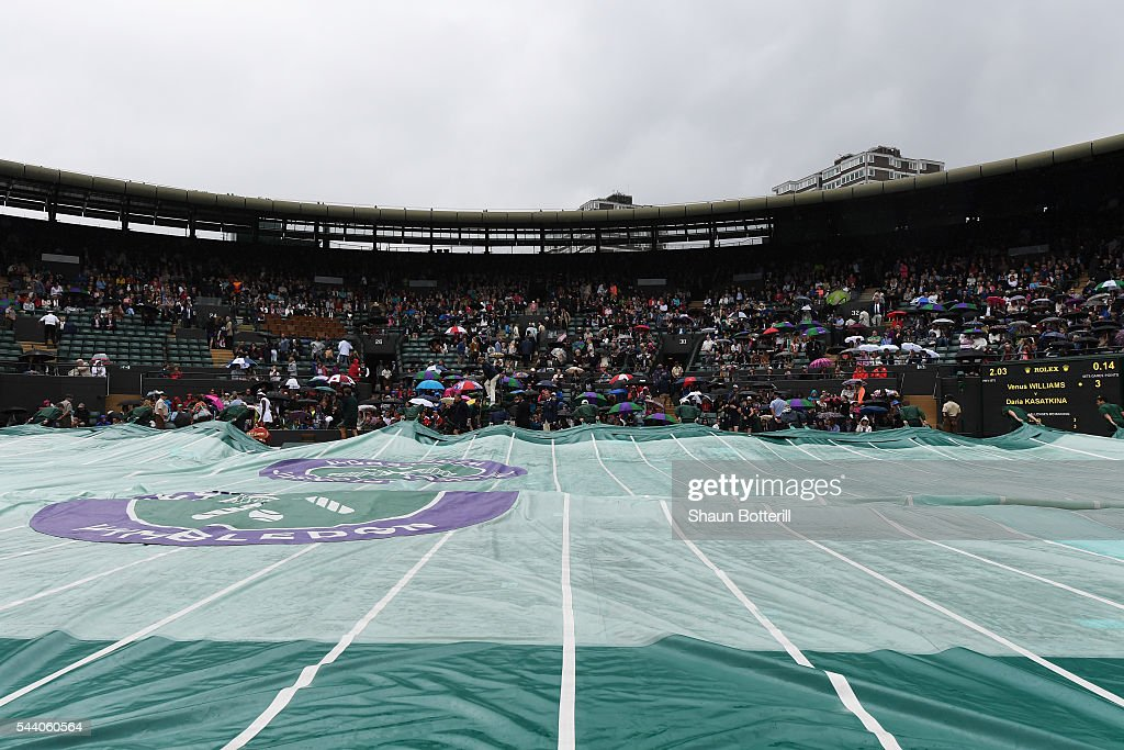 Grounds staff pull the covers over court one on day five of the Wimbledon Lawn Tennis Championships at the All England Lawn Tennis and Croquet Club on July 1, 2016 in London, England.
