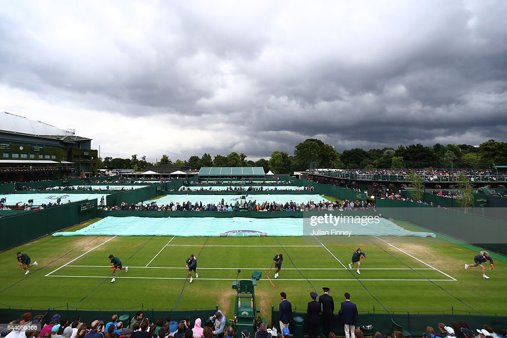Grounds staff pull the covers over the courts on day five of the Wimbledon Lawn Tennis Championships at the All England Lawn Tennis and Croquet Club on July 1, 2016 in London, England.