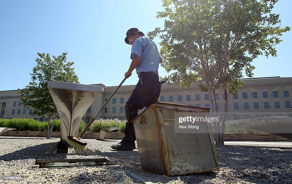 Groundskeeper Lucas Guzman washes the glowing light pool of a bench at the Pentagon Memorial June 28, 2011 in Arlington, Virginia. This year is the 10th anniversary of the September 11 terrorist attacks, in which 184 people were killed at the Pentagon.