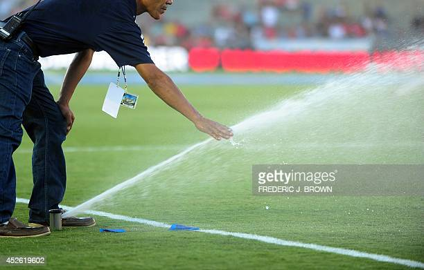 Groundskeeper Martin Rodriguez touches the water coming out of a sprinkler as the pitch is watered down before kickoff in the Chevrolet Cup match...