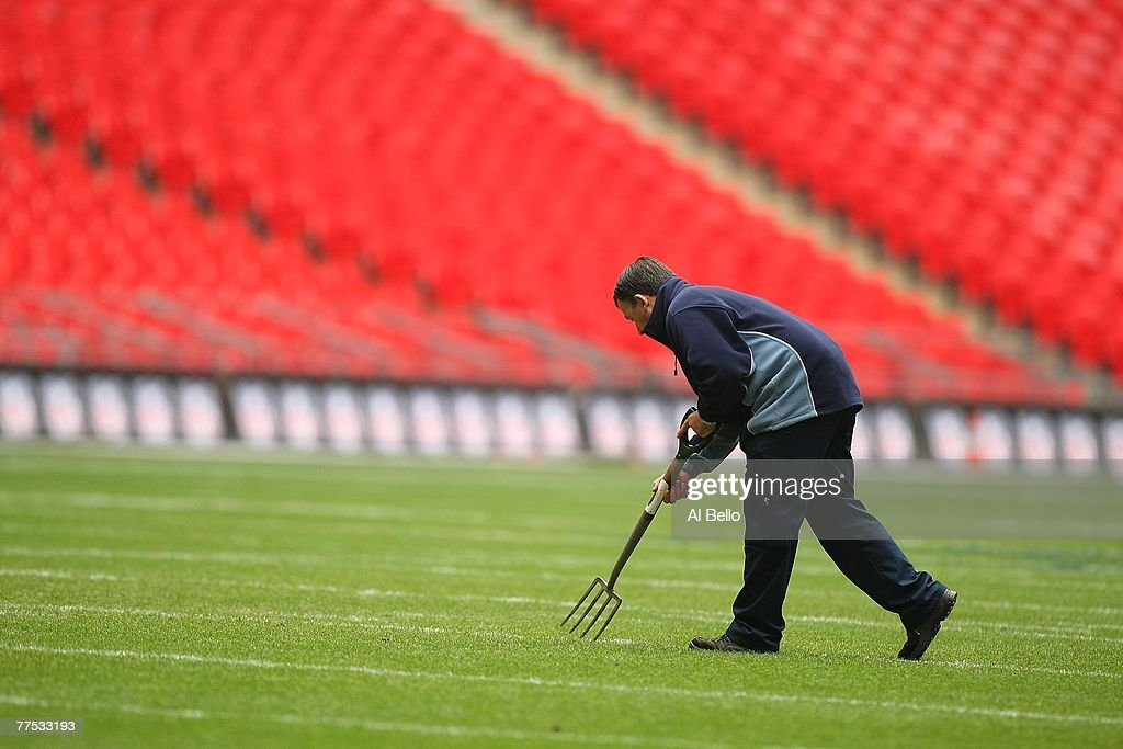 A groundskeeper replaces the divots in the field after practice a day before the game between the Miami Dolphins and the New York Giants on October...