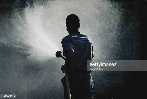 A groundskeeper sprays water from a hosepipe onto the clay court and the net during the French Open Tennis Championship on 1st June 1994 at the Stade...