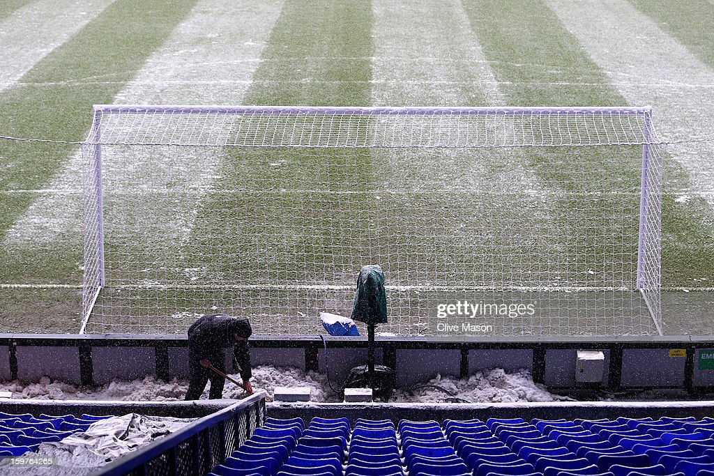 A groundsman clears snow from the stand ahead of the Barclays Premier League match between Tottenham Hotspur and Manchester United at White Hart Lane on January 20, 2013 in London, England.